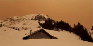 Sandstormen färgar himlen orange. Bild från Aosta-dalen, Italien. Foto: Planetski